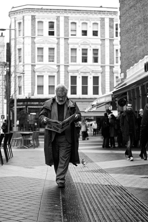 Walk the line. Man reading a news paper while walking, South Kensington, London